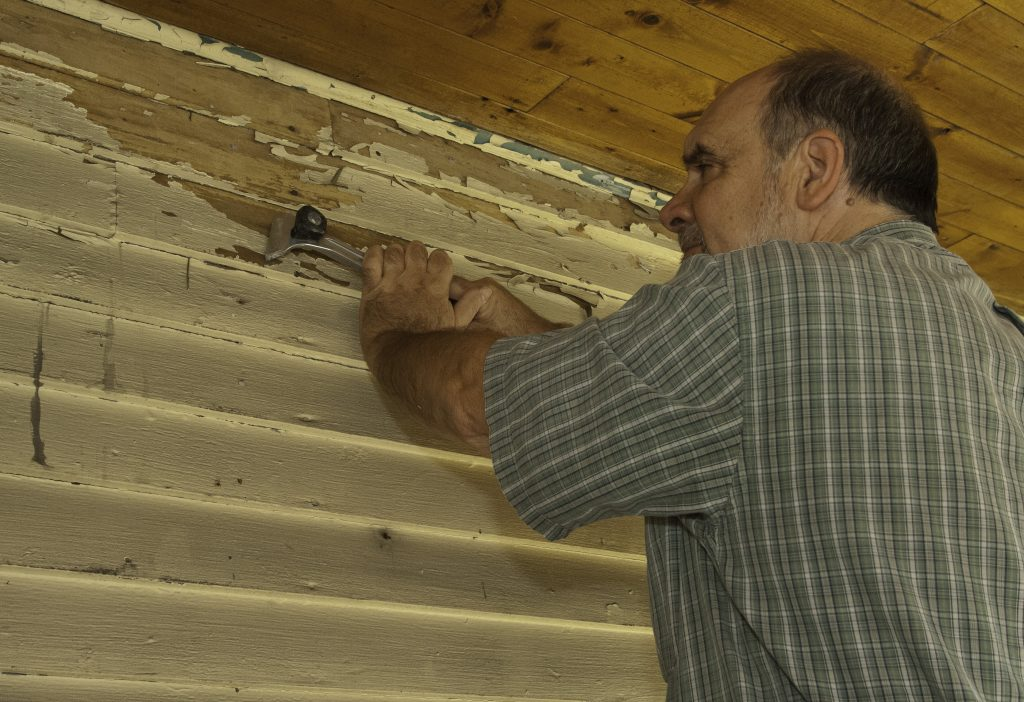 Scraping paint from vintage clapboard
