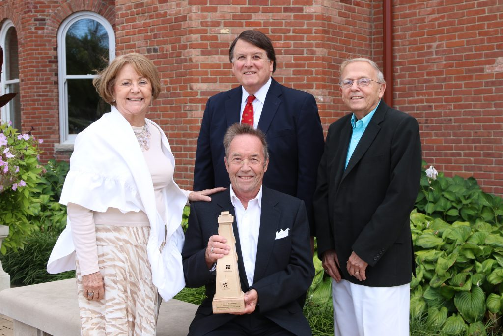 Indiana Landmarks Honorary Chairman Randall Shepard (standing center) presented the nonprofit Servaas Memorial Award to the Preservation Society of Union City IN-OH, represented by officers Ted Leahey (seated center), and Betsy and Allen Jefferis.
